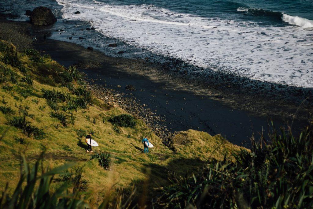 Praia de areia preta Maori Bay em Muriwai na Nova Zelândia.