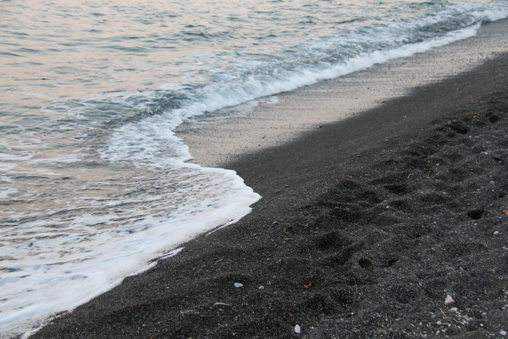 Praia Perissa em Santorini na Grécia. Praia de areia preta